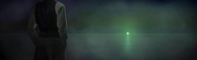 A man stands on a dock at night, gazing across the dark waters to a green light shining in the distance.