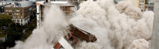 A building collapses in smoke and dust.