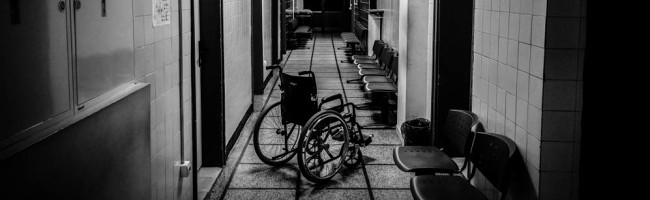 A black and white hospital corrodor, empty chairs wearing the thinnest of cushons. A lone wheelchair takes center stage, waiting to be used.