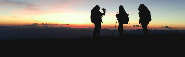 the silhouettes of three backpackers stand against the sunset