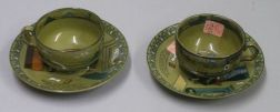 "Two Buffalo Pottery Emerald Deldare Ware ""Dr. Syntax and Bookseller"" Saucers and a   Pair of Deldare Ware Cups"