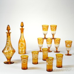 Two Bohemian Amber Etched Glass Decanters and Eleven Glasses
