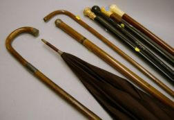 Five Walking Sticks, Two Sterling Silver Embellished Canes, and a Maroon Silk   Parasol