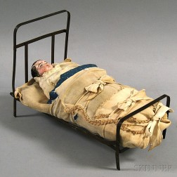 Carved and Painted Wood Doll in an Iron Bed
